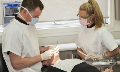 Dentist and assistant with patient in chair